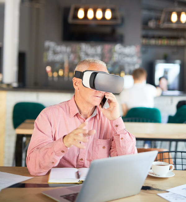 Business man wearing VR headset with laptop on phone